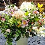 A variety of summer garden flowers in a milk glass vase.
