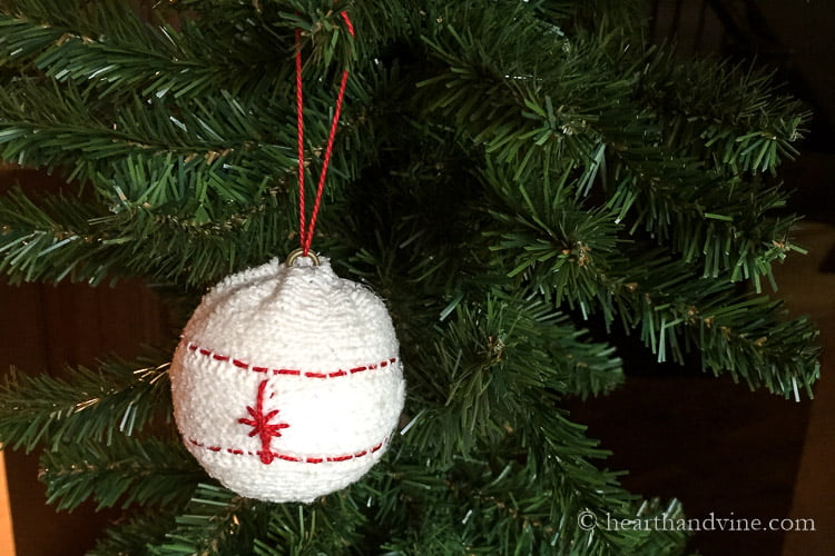 Sweater ornament with red stitching on tree