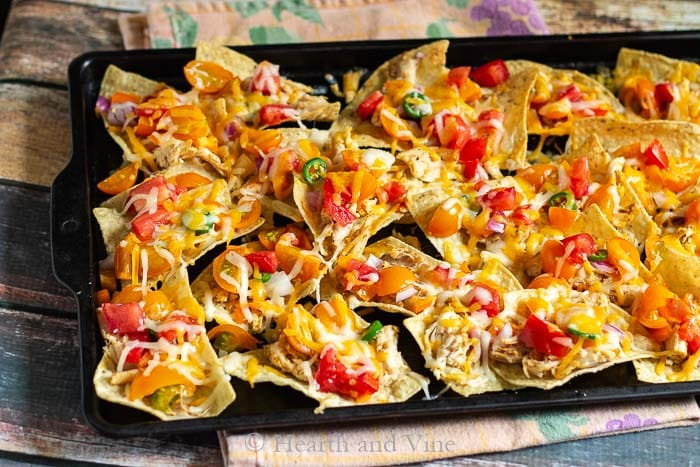 Low acid tomato chicken nachos on baking sheet