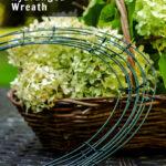 Flores do centro das atenções em uma cesta ao lado de uma armação de guirlanda de arame, arame floral e podadores em uma mesa.