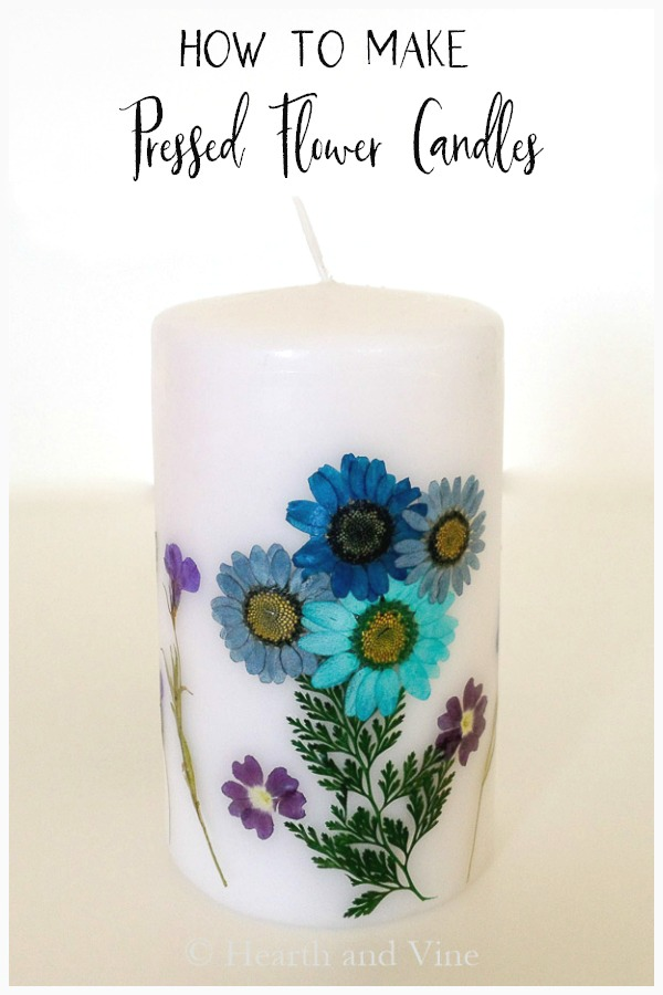White pressed flower candle with blue flowers