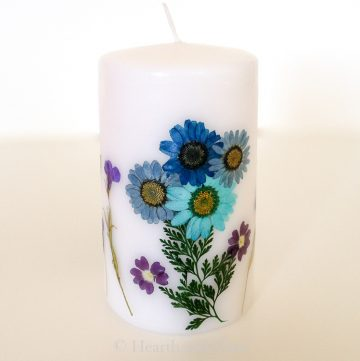 Pressed flowers on white pillar candle