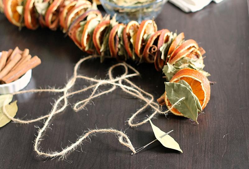 Stringing bay leaf on orange garland
