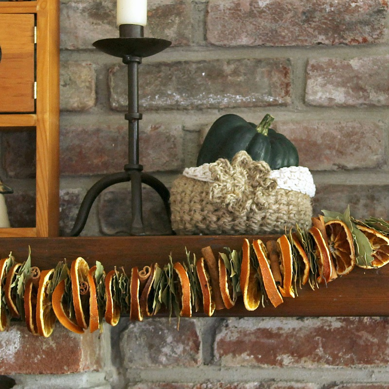 Close up view of dried orange slice, cinnamon and bay garland on mantel