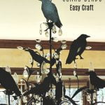 Black paper birds on a chandelier.