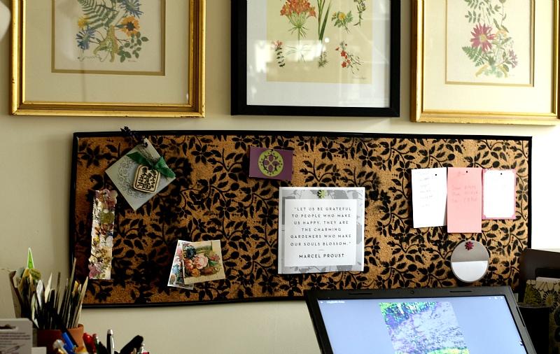 Black floral cork bulletin board hung horizontal on a wall.