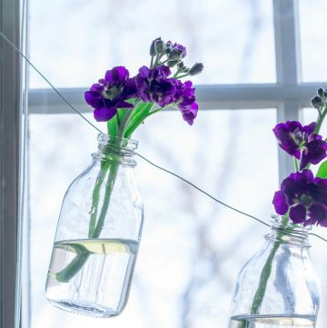 Glass bottle vase garland with purple flowers