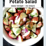 Bowl of red potato salad with dill, red onions and lemon.