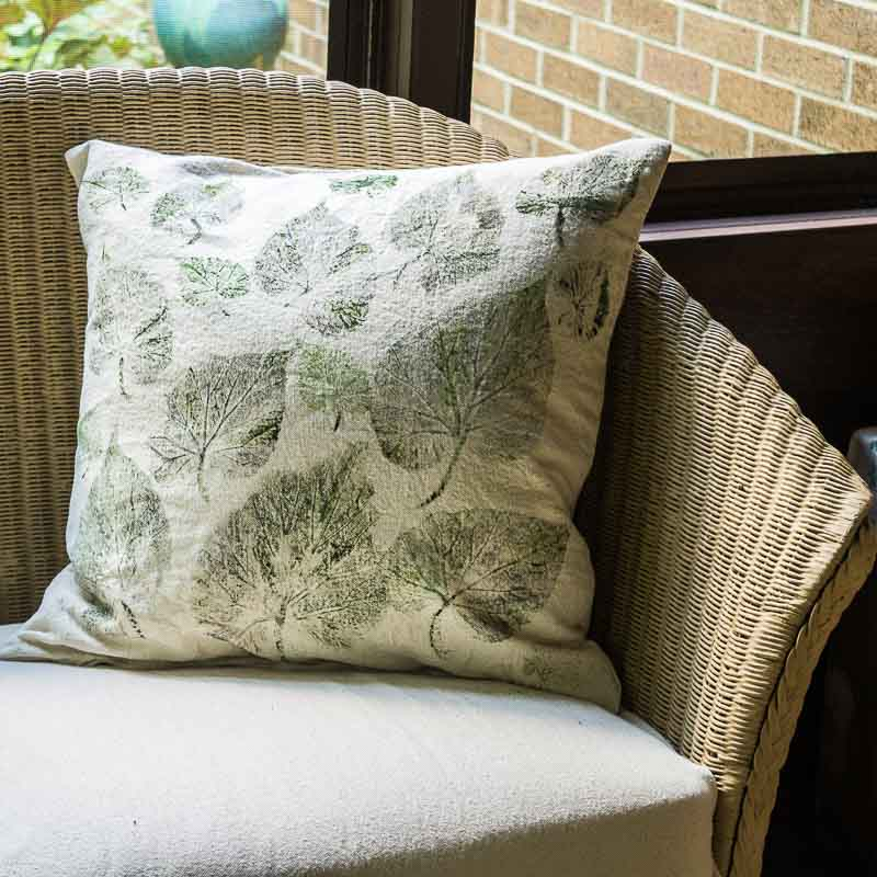 Leaf print drop cloth pillow on couch in screened in porch.