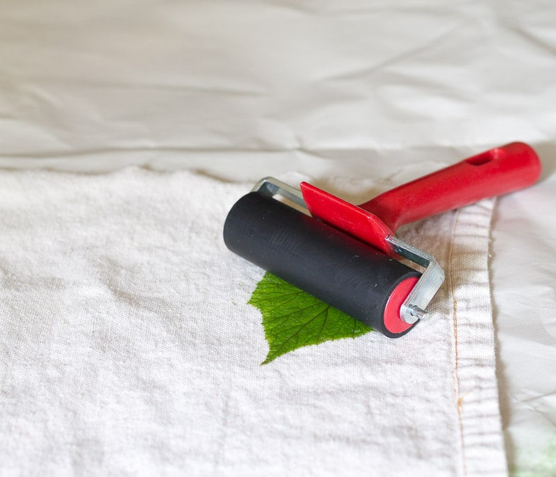 Red brayer rolling on leaf on drop cloth fabric.