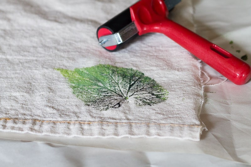 Print of leaf on drop cloth material next to a brayer.