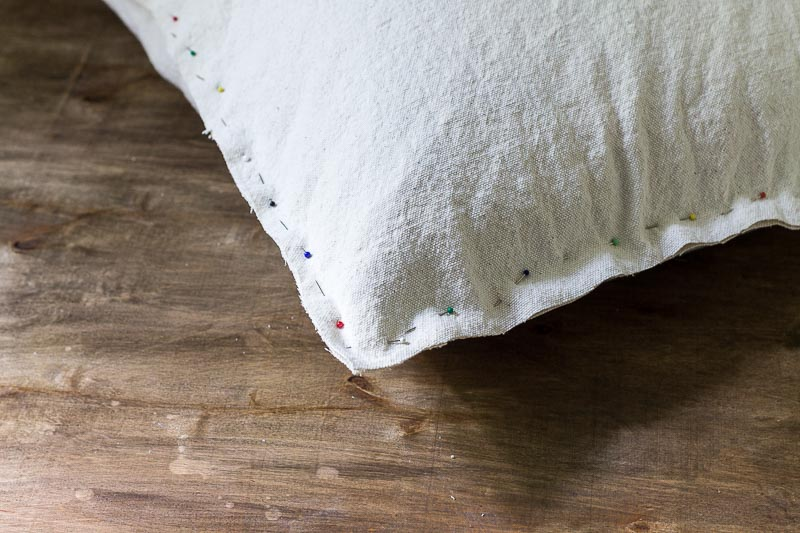 Trimmed pinned drop cloth fabric around old pillow.