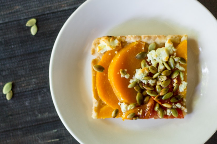 Butternut squash tart with tomatoes, goat cheese and pepitas is feast for the eyes and makes a great appetizer or delicious meal.