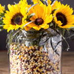 Apothecary jar with color popcorn kernels and sunflowers