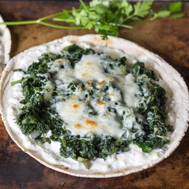 This recipe for spinach and ricotta pita bread pizza is easy to make and is a healthy alternative to traditional pizza with fewer carbs and more protein.