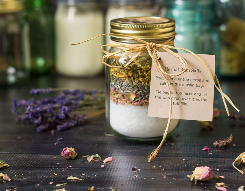 Mason jar of bath salts and layers of herbs with a raffia ribbon and instruction tag.