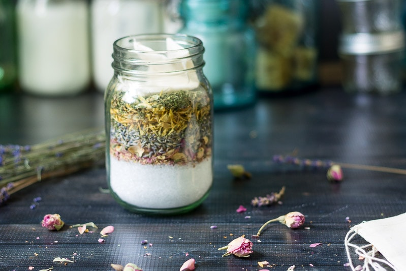 Herbal bath salts in a pint mason jar with scattered dried rosebud and lavender on the table.