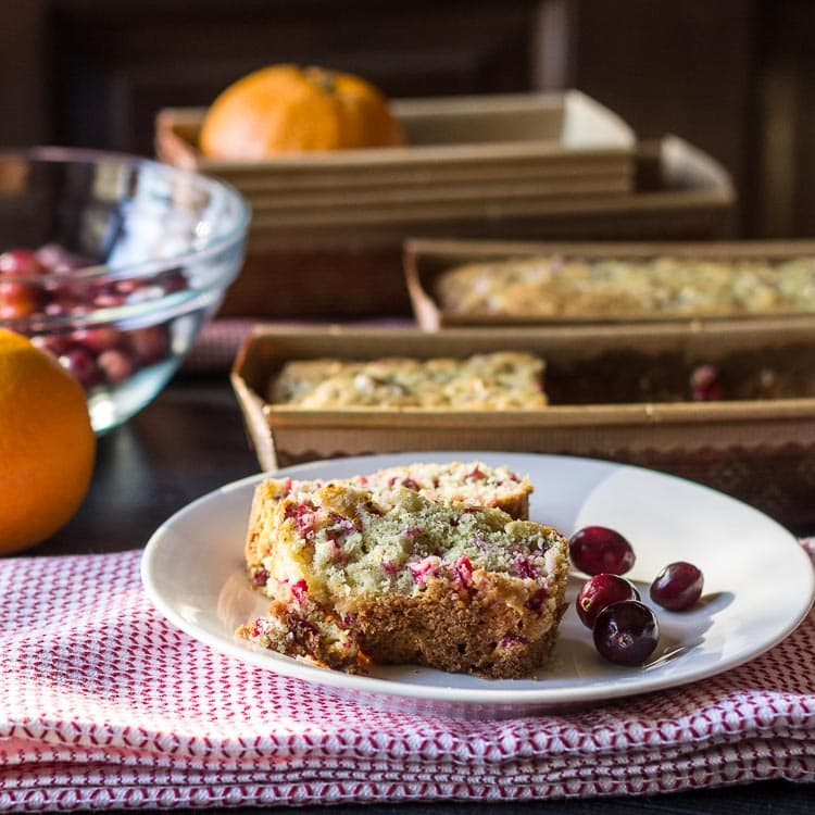 Cranberry orange bread slices with cranberries and loaves.