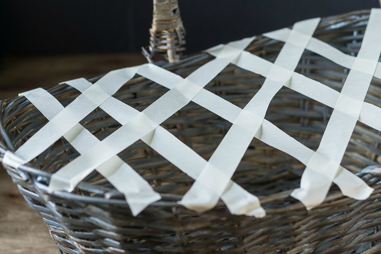 Using tape to create lattice on basket to hold flowers