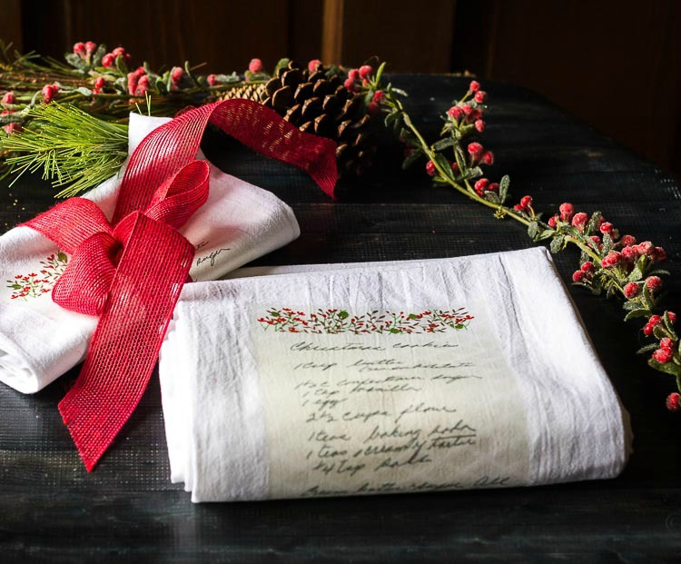 Handwritten Christmas cookie recipe transferred onto a tea towel, next to one rolled up and wrapped with a red ribbon. Pine con and frosted berry garland in the background.