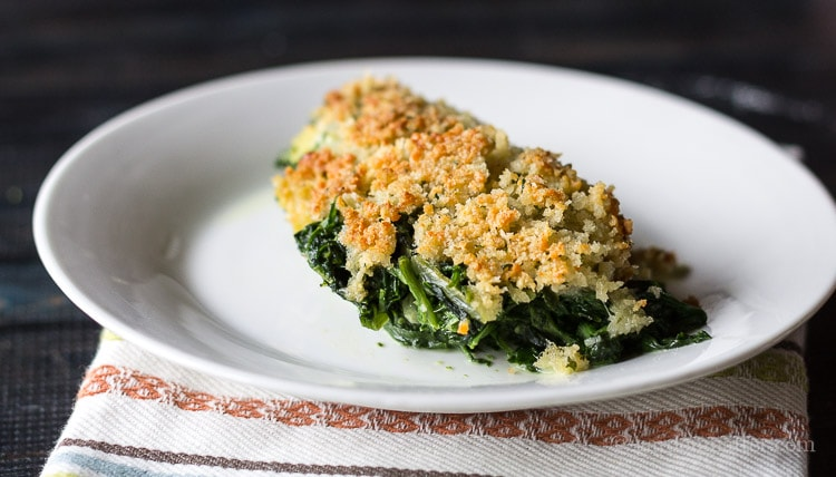 A serving of cream spinach casserole with panko bread crumbs.