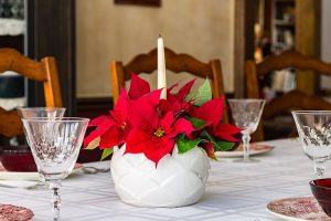 An easy centerpiece made with poinsettia flowers and a candle