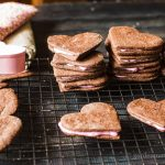 Recipe for chocolate heart cookies filled with pink icing perfect for Valentine's Day.