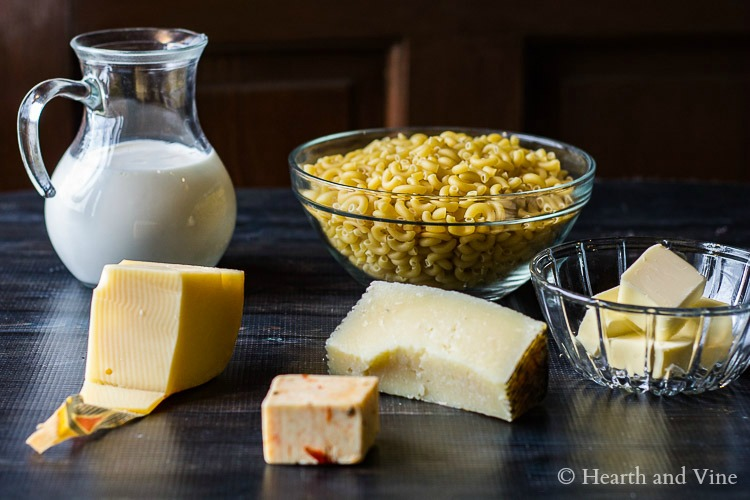 Different blocks of cheese, milk, butter and elbow macaroni.