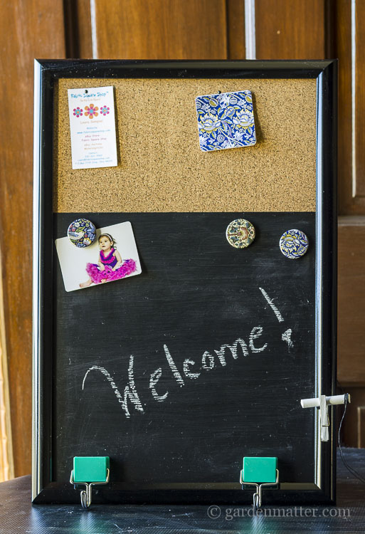 Message board with cork, chalkboard area and hanging chalk.