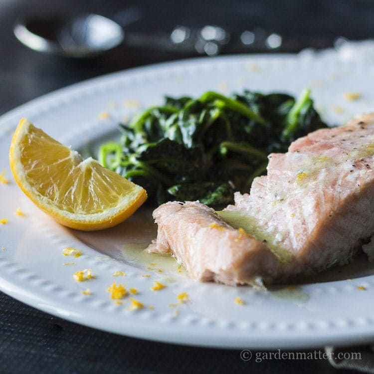Meyer lemon butter sauce on baked salmon and wilted fresh spinach.