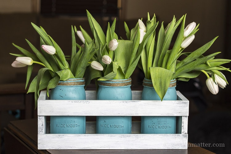 Blush tulips in blue mason jars in a white chalk painted wood crate.