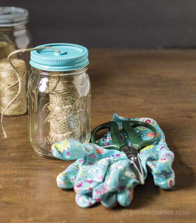 Gift set of mason jar dispenser, garden gloves and floral shears.