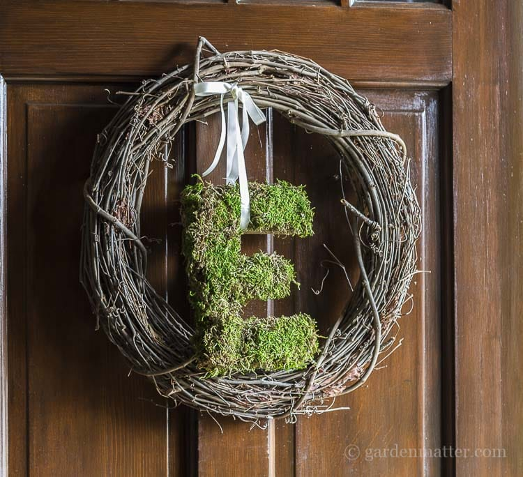 Hanging letter E wreath covered in natural moss for front door decor.