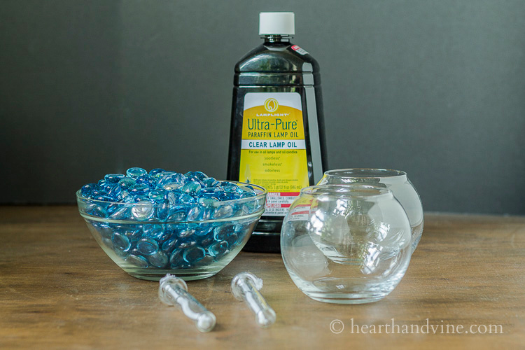 Materials to make patio oil lantern. Blue gems, glass vases, lamp oil and inserts.