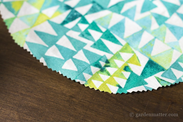 Cut circle of fabric with pinking shear to prevent fraying.