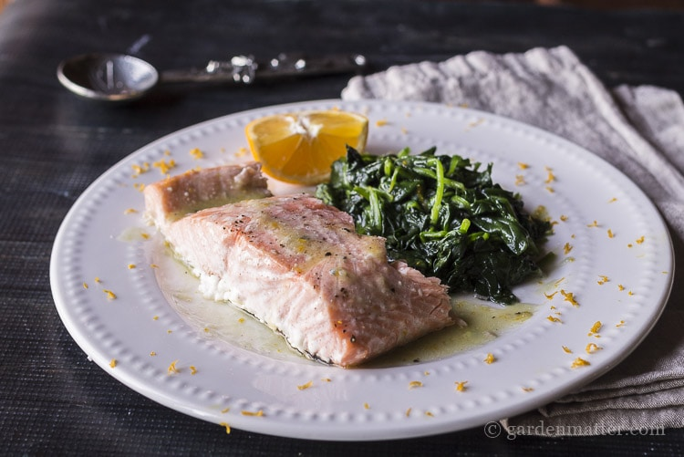 A plate of wilted spinach and salmon with meyer lemon butter sauce