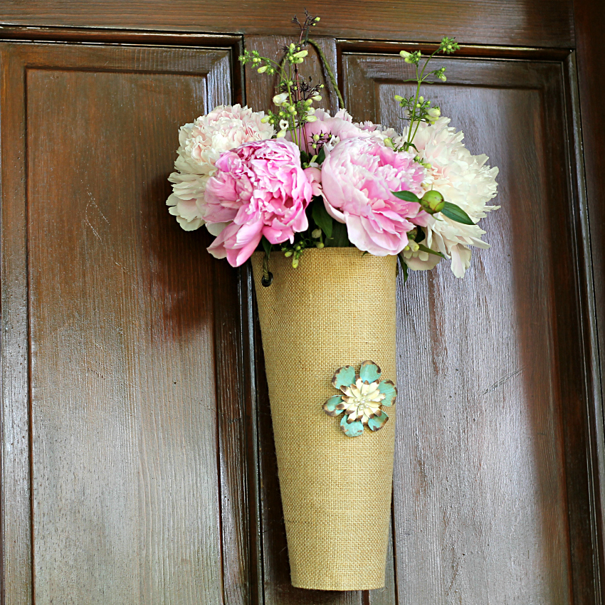 Peonies in a burlap vase on door wit an aqua and cream floral brooch.
