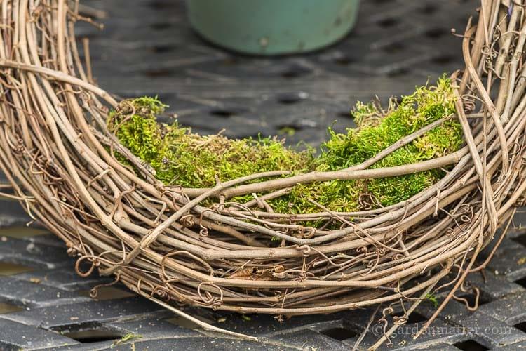 Sheet moss set into grapevine wreath.