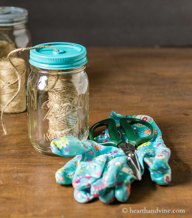 garden gloves scissors and mason jar with jute