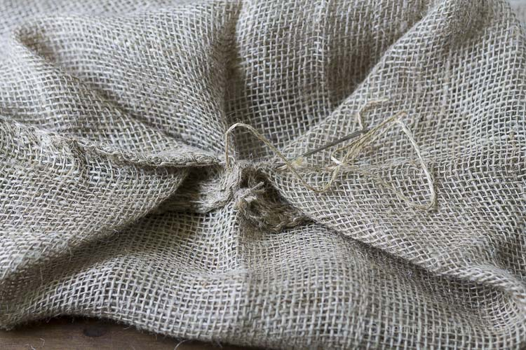 Corners of burlap sack sewn together to create bottom.