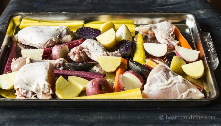 chicken parts, potatoes and tri-colored carrots on sheet pan.