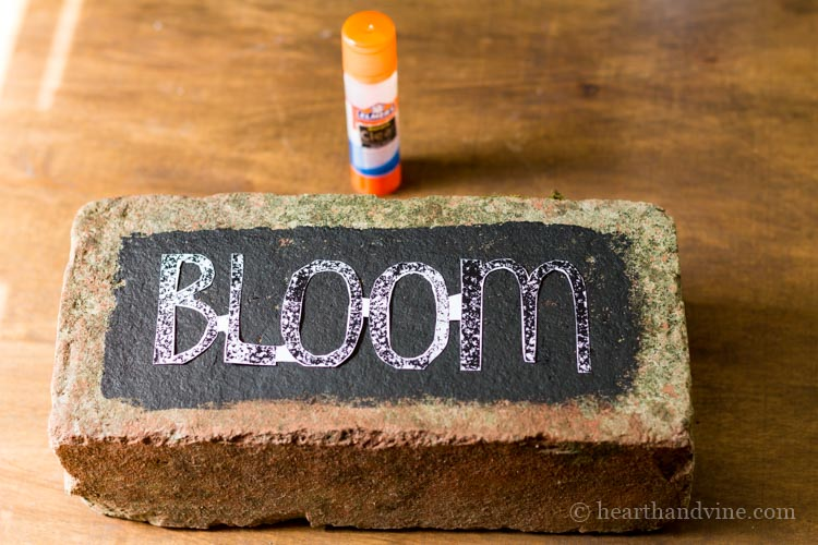 Brick with black paint and the word bloom glued on.