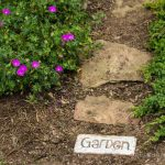 Garden brick word art at the beginning of stone path.