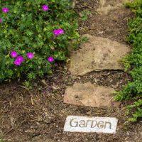 Garden brick word art at the beginning of stone path.