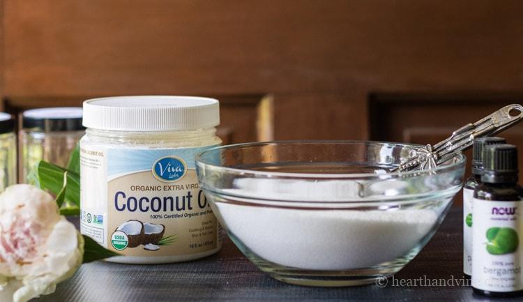 Materials for blush pink sugar body scrub recipe. Sugar, coconut oil and essential oils.