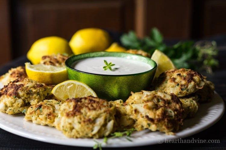 Party dish with mini crab cakes and dipping sauce.