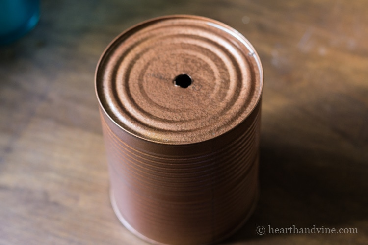 Tin can with drilled hole and spray painted copper.