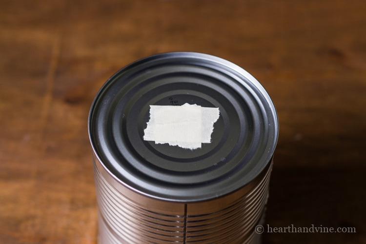 Empty tin can with masking tape on center