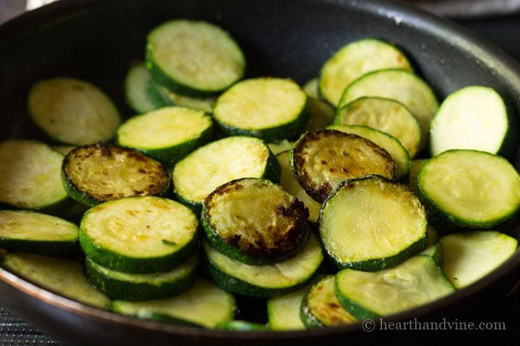 Sauteed zucchini sliced in pan.