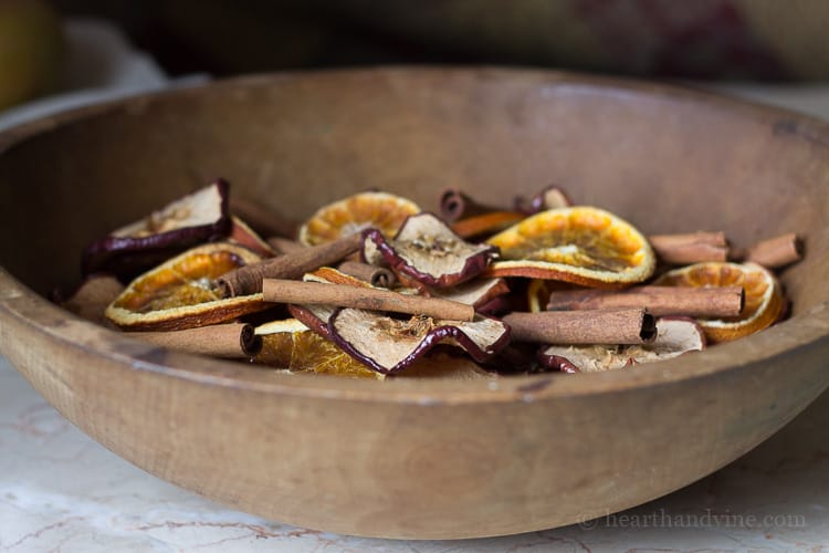 Homemade potpourri made with natural apples, orange slices and cinnamon sticks in a large wooden bowl.
